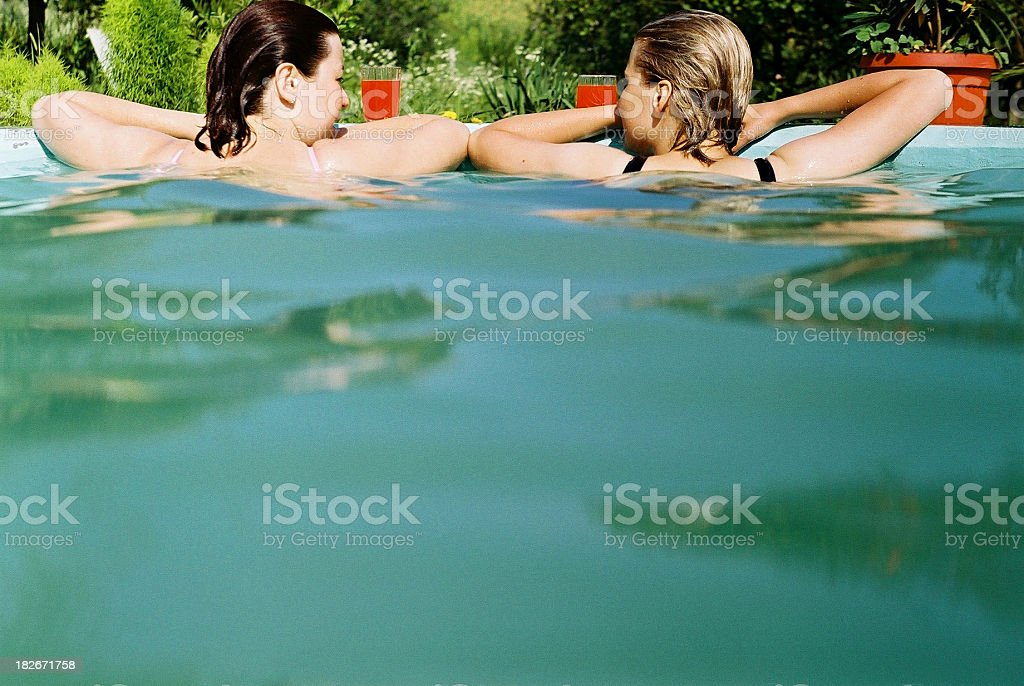 Girls relaxing in the swimming pool stock photo