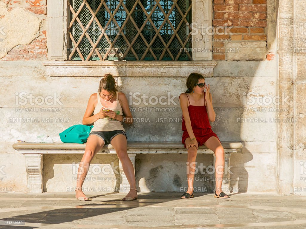Girls rest from the intense summer heat of Venice, Italy stock photo