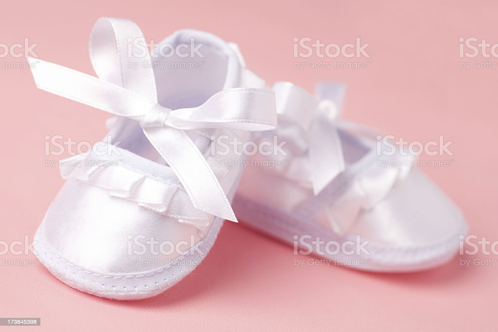 Girl's satin newborn baby shoes on a pink background stock photo