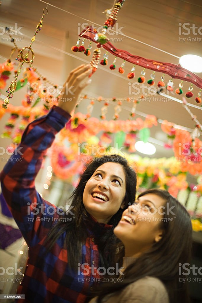 Girls shopping wall hanging at a decorated shop in festival. stock photo