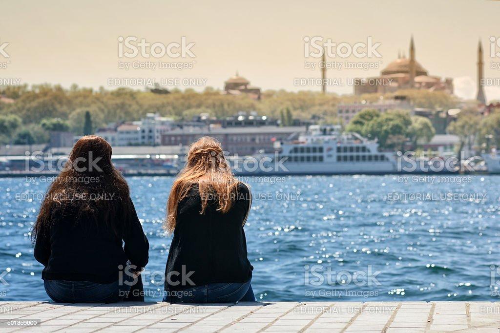 Girls Sitting At Coastline, Istanbul, Turkey stock photo