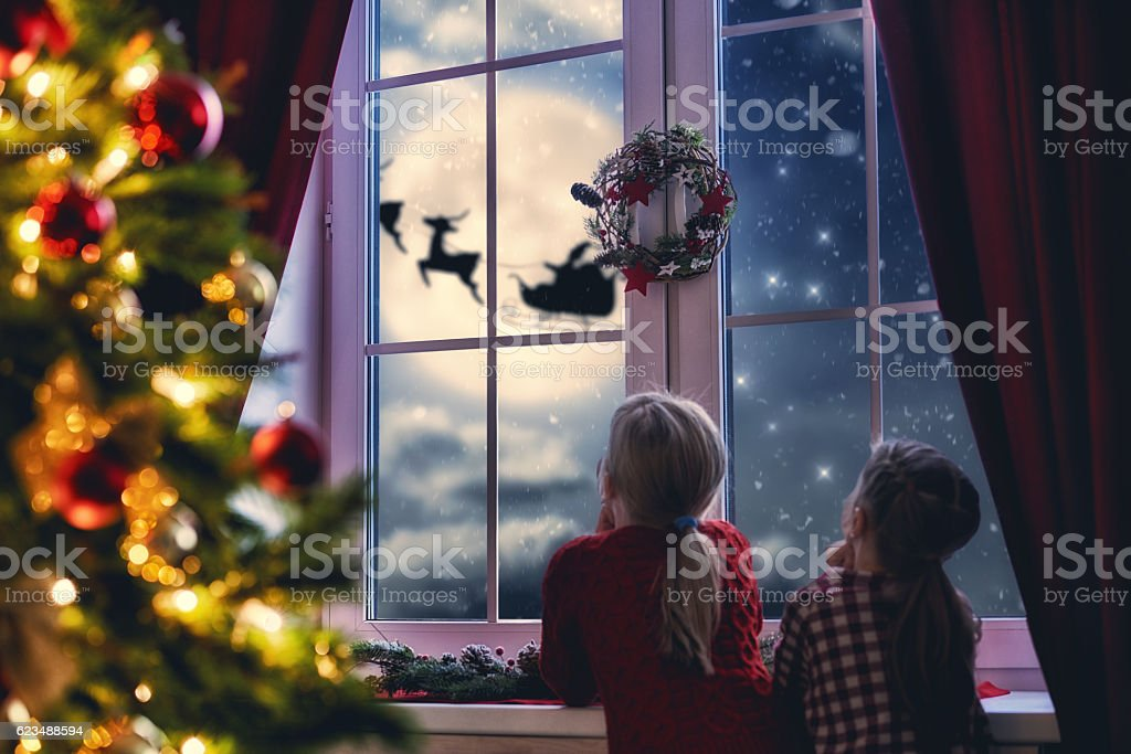 girls sitting by window and looking at Santa stock photo