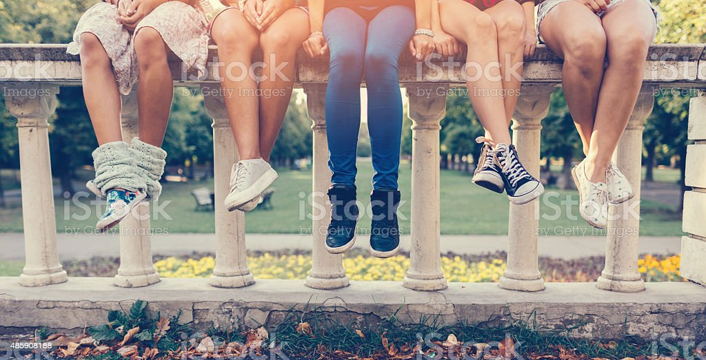 Girls sitting in a row stock photo