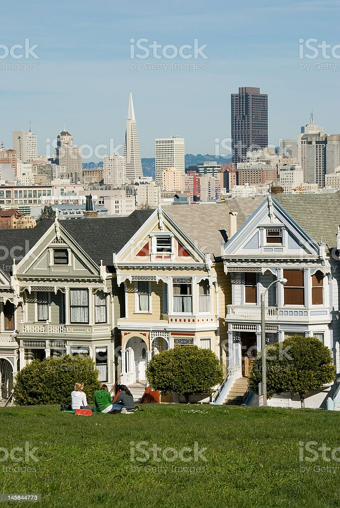 Girls Sitting in Front of the 'Painted Ladies' Victorian Houses stock photo