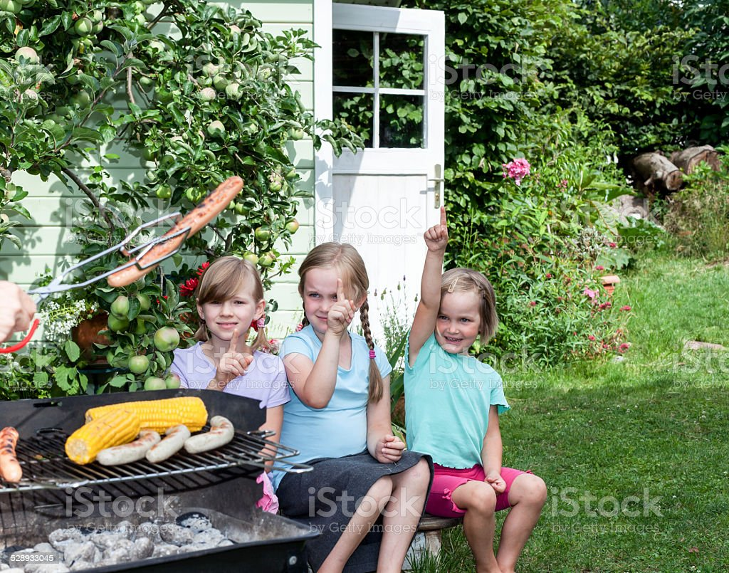 Girls sitting in garden waiting someone offering barbequed sausage stock photo