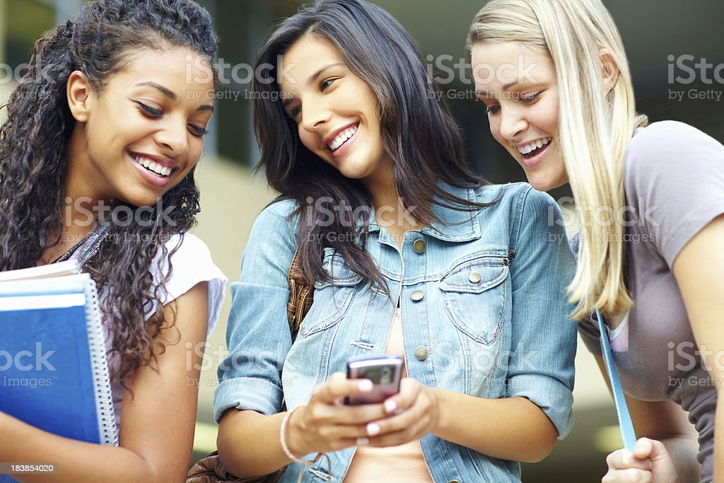 Girls smiling over a funny text message royalty-free stock photo