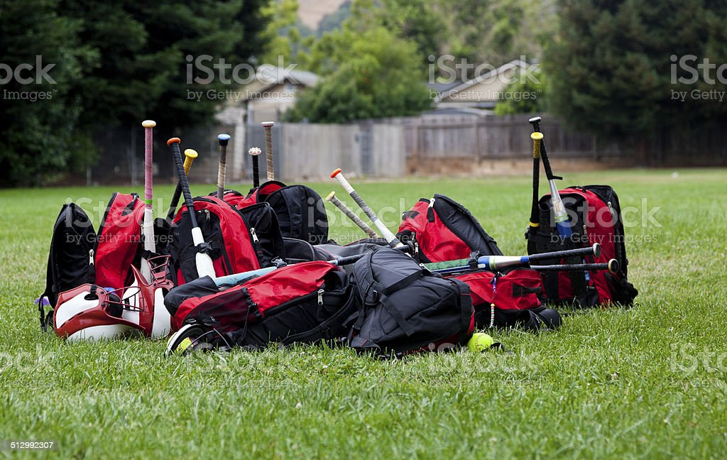 tween girls\' softball team equipment laying on the grass