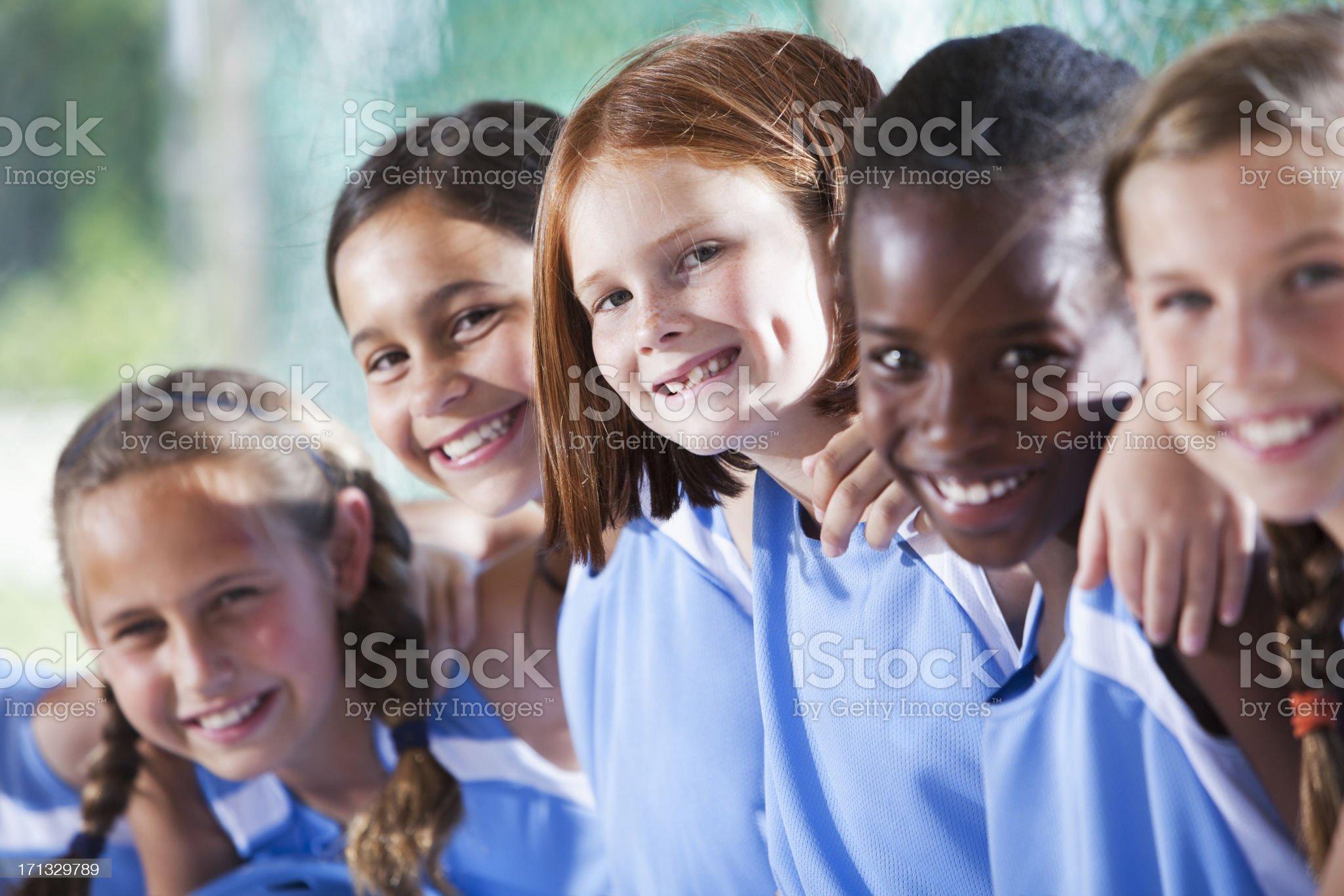 Girls softball team sitting in dugout royalty-free stock photo