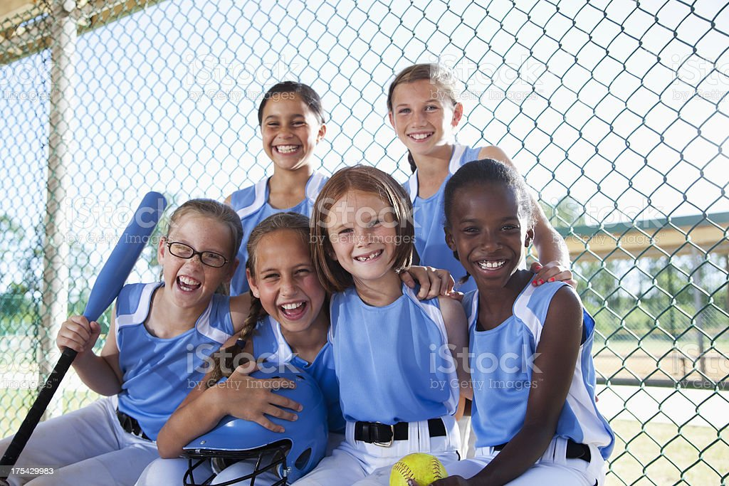 Girls softball team sitting in dugout stock photo