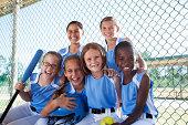 Girls softball team sitting in dugout