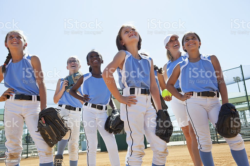Multi-ethnic girls softball team standing on ball field . Focus on...