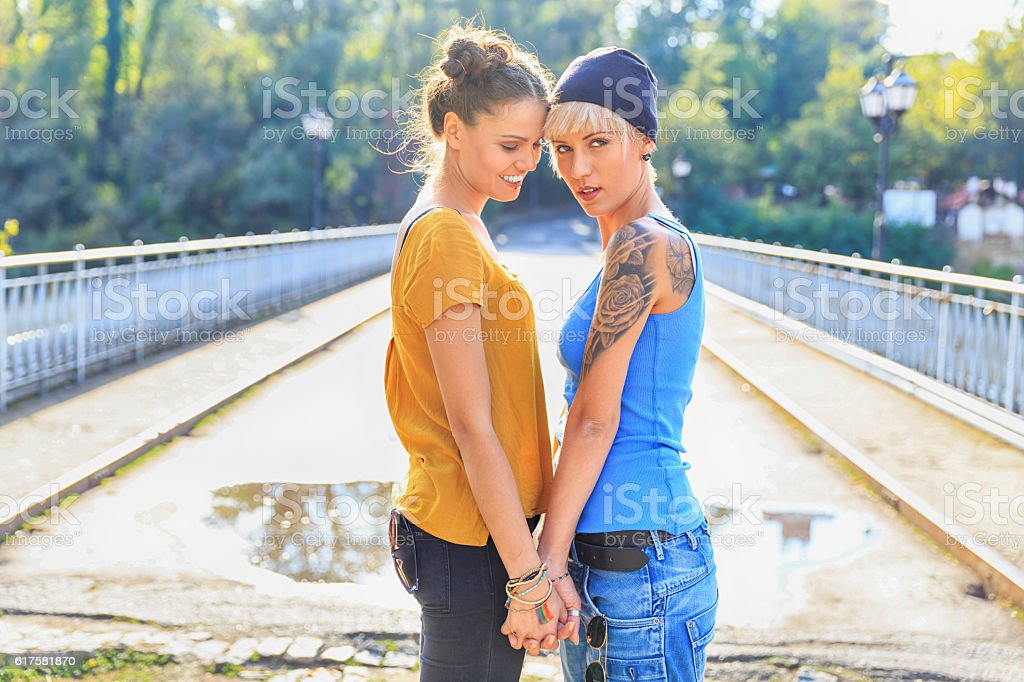 Girls standing face to face on bridge and holding hands stock photo