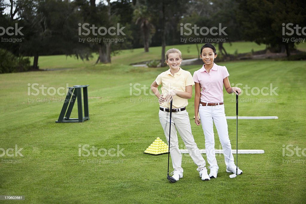 Girls standing on golf driving range stock photo