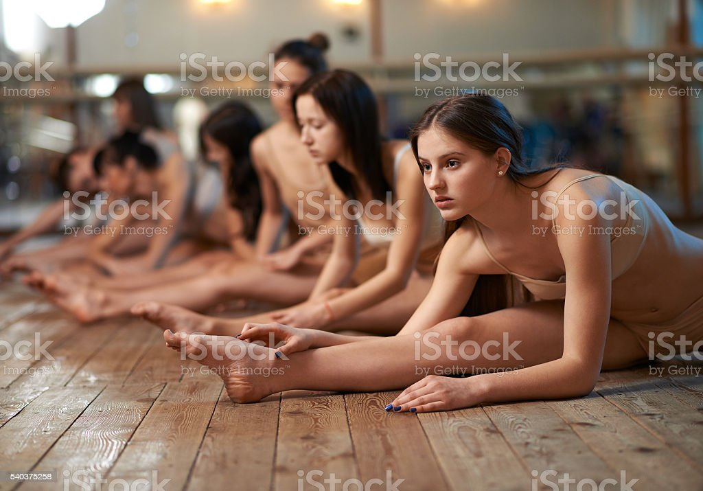 girls stretch his legs in splits on dance lessons stock photo