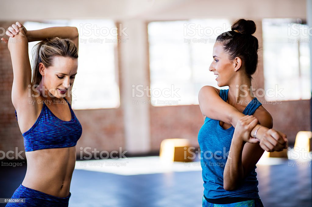 Girls stretching sholder muscles after a gym workout at gym stock photo