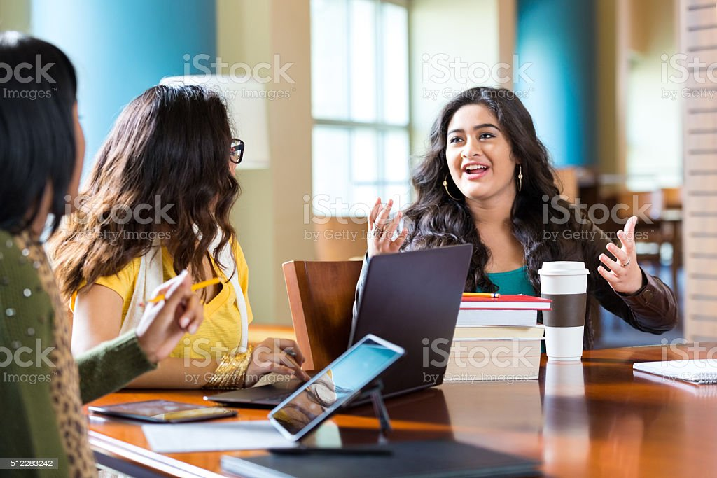 Girls studying for high school or college exam in library stock photo