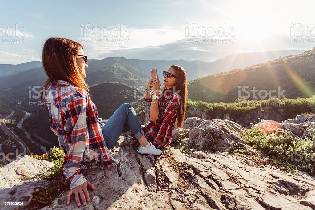 Girls taking photos on the mountain peak stock photo