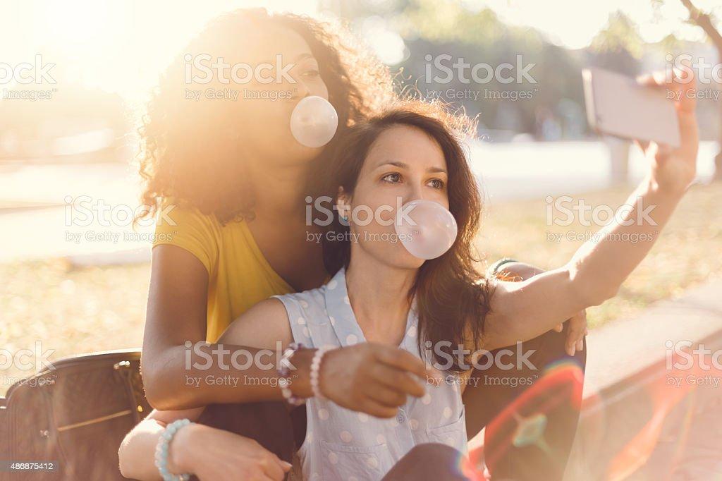 Girls taking selfie in the park stock photo
