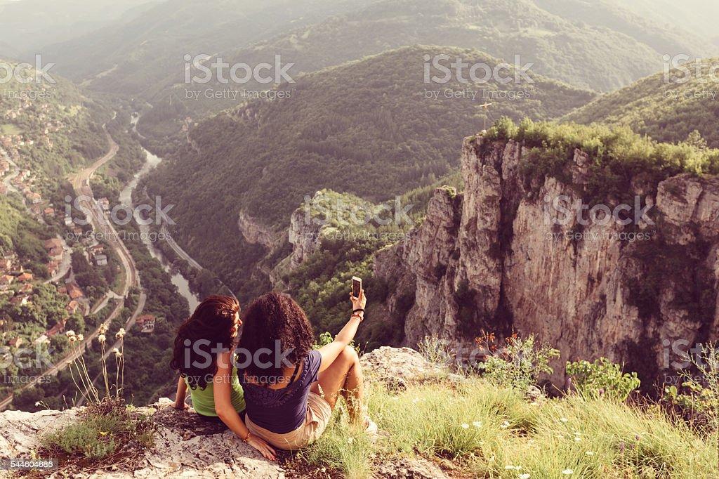 Girls taking selfie on the mountain peak stock photo