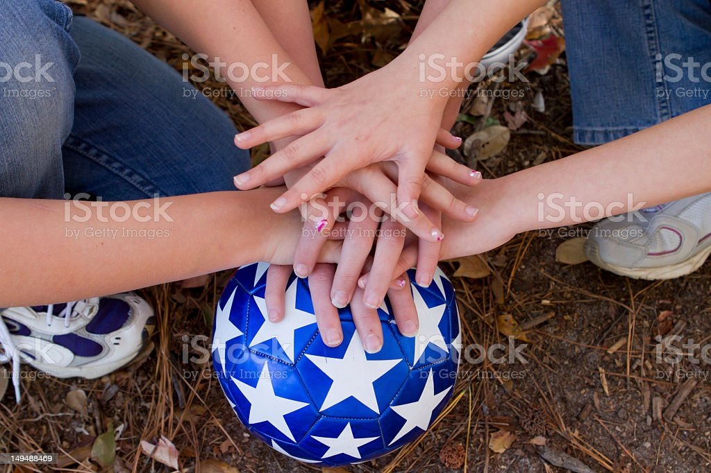 Girls team stacks their hands on a soccer ball. stock photo