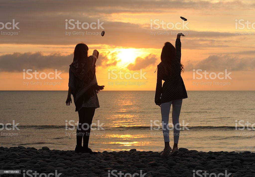 Girls Throwing Pebbles  into the Sea stock photo