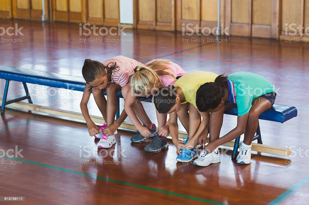Girls tying shoe laces in basketball court stock photo
