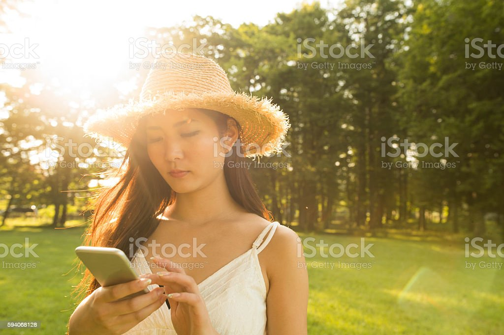 Girls use the smart phone in the sunset. stock photo
