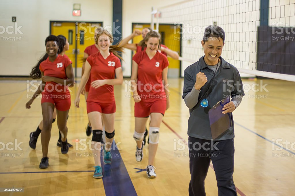 Girls volleyball players with coach after big win stock photo