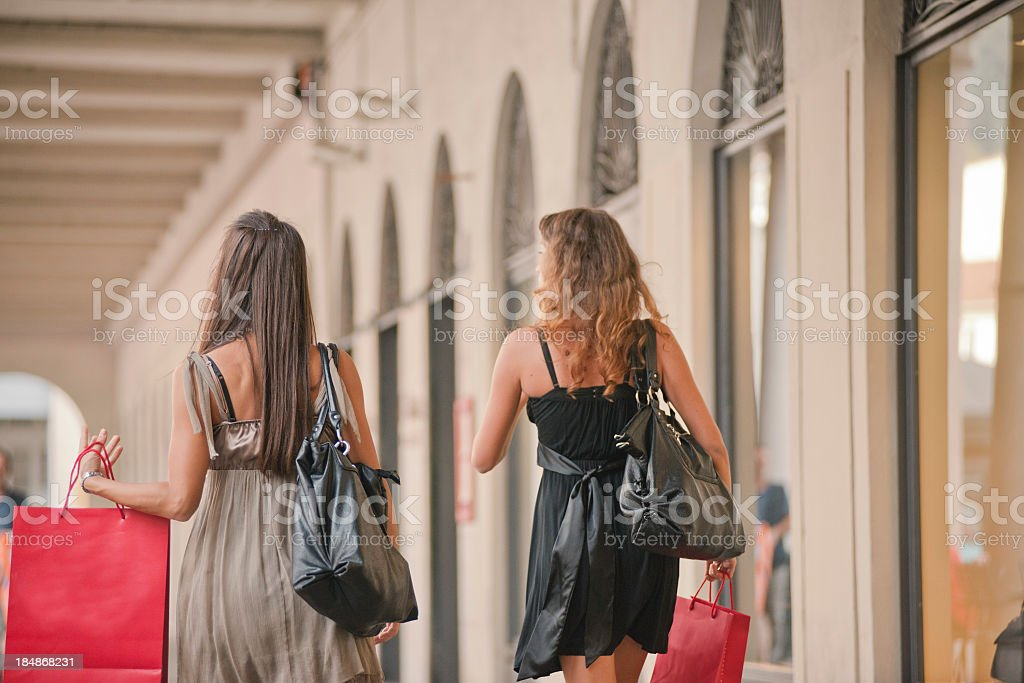 Girls walking on narrow street with shopping mall royalty-free stock photo