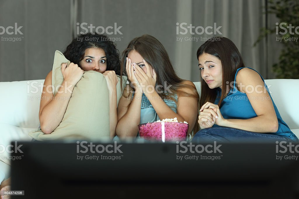 Girls watching a terror movie on tv stock photo