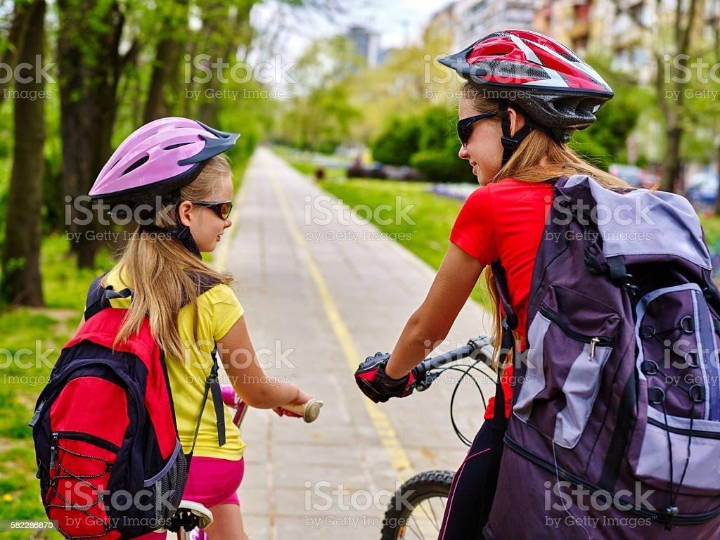 Girls wearing bicycle helmet and rucksack ciclyng . stock photo