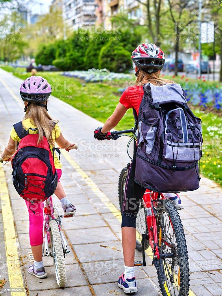 Girls wearing helmet and rucksack ciclyng bicycle. stock photo