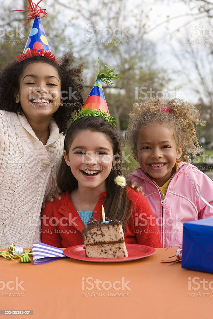 Girls (5-10) wearing party hats, slice of cake on table stock photo