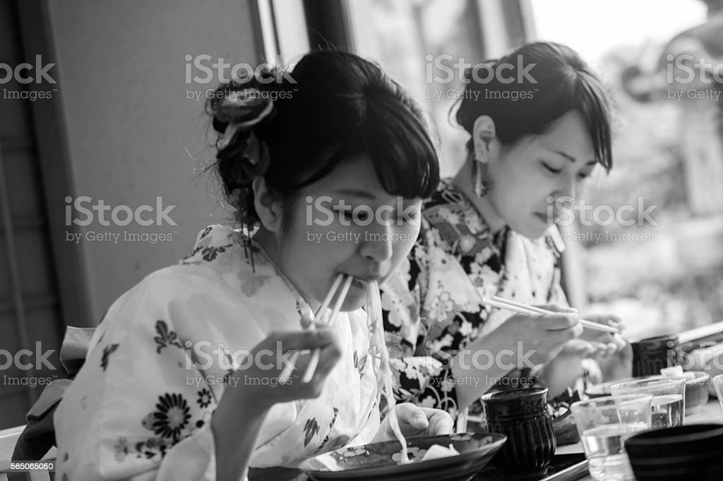 girls wearing traditional kimono costume eating noodle in kyoto japan stock photo