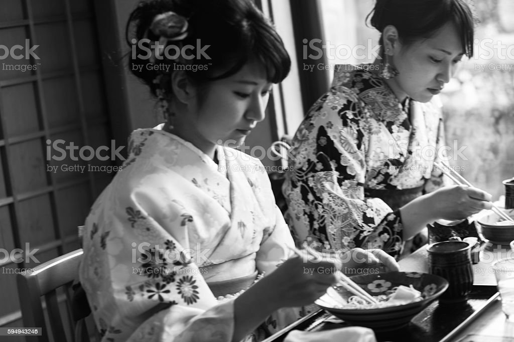 girls wearing traditional kimono eating noodle in kyoto japan stock photo