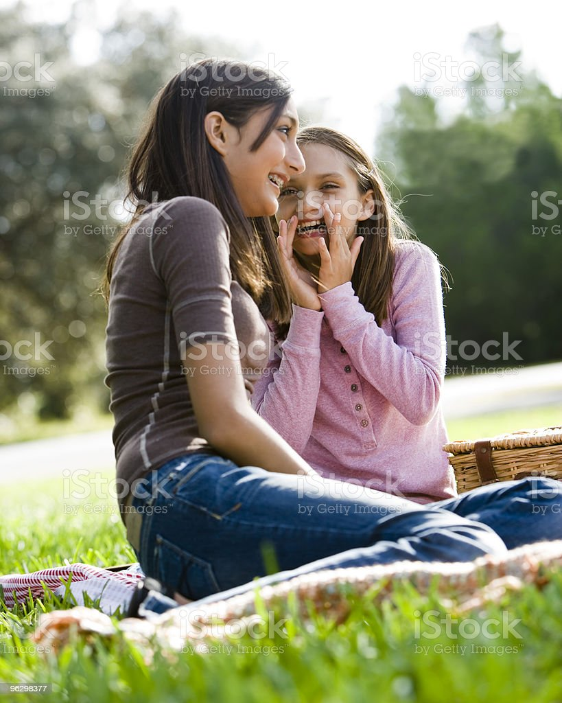 Girls whispering to each other at picnic in park royalty-free stock photo