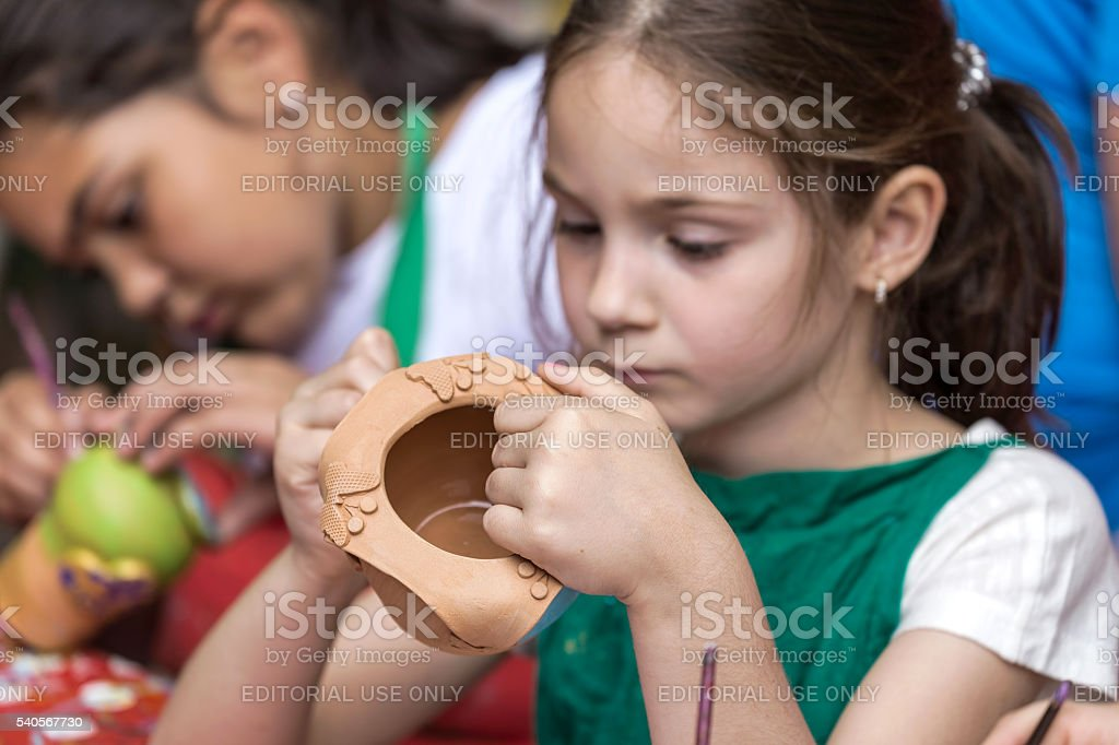 Girls who paints a ceramic bowl stock photo