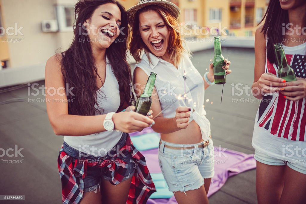 Girls with beer bottles and sparklers on a rooftop party stock photo