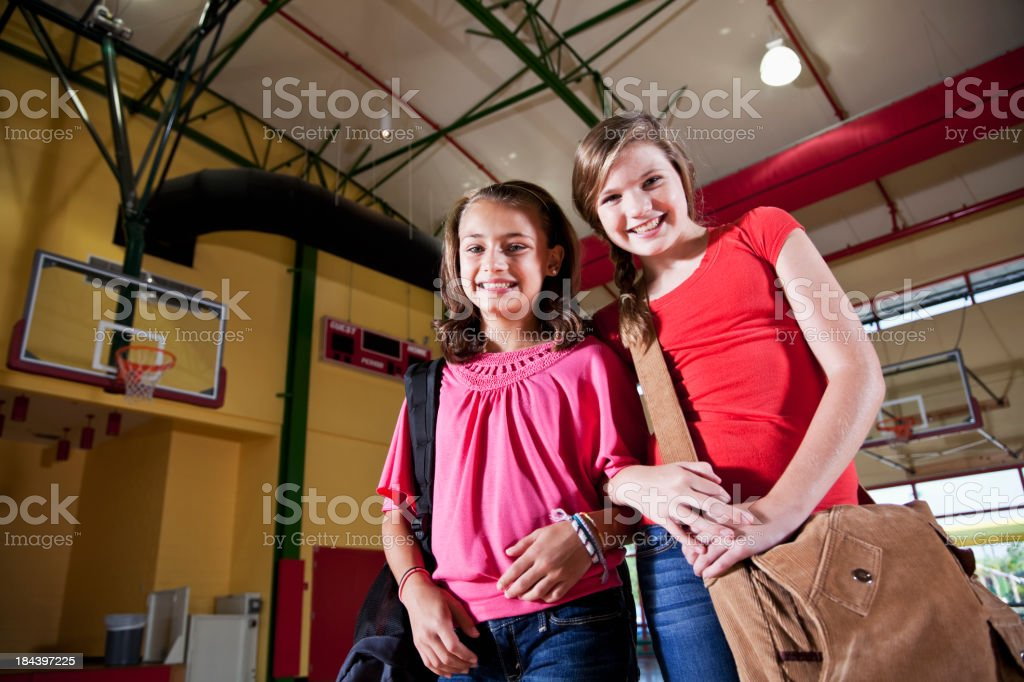 Girls with bookbags standing in school gym stock photo