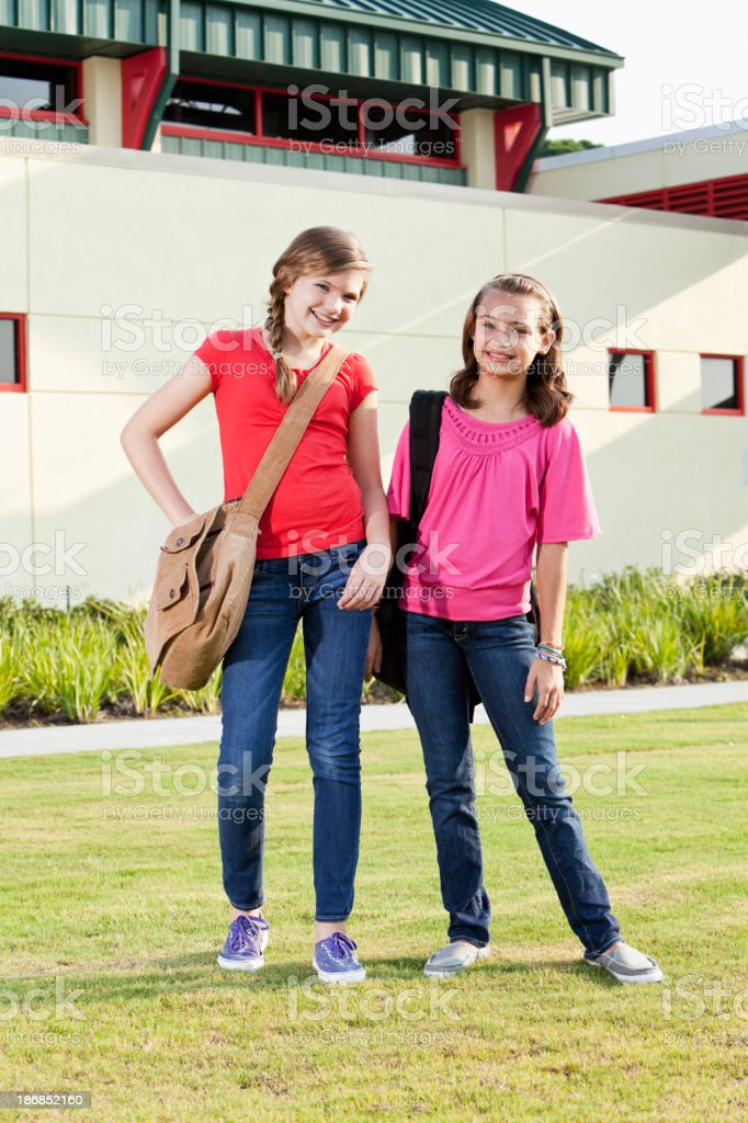 Girls with bookbags standing outside school stock photo