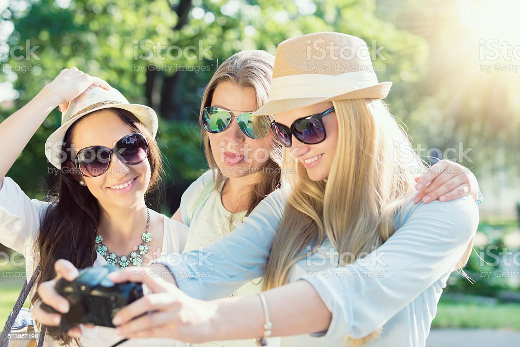 girls with camera taking self-portrait on their travel vacation stock photo