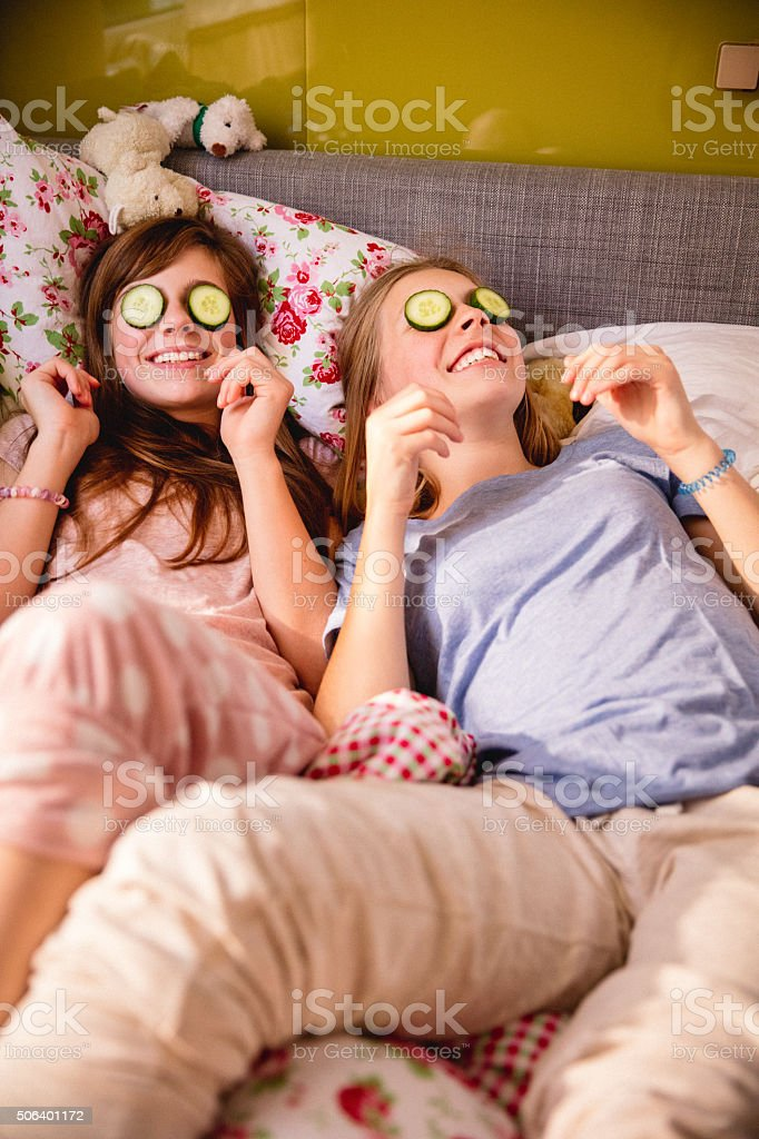 Girls with cucumber on their eyes as a beauty treatment stock photo