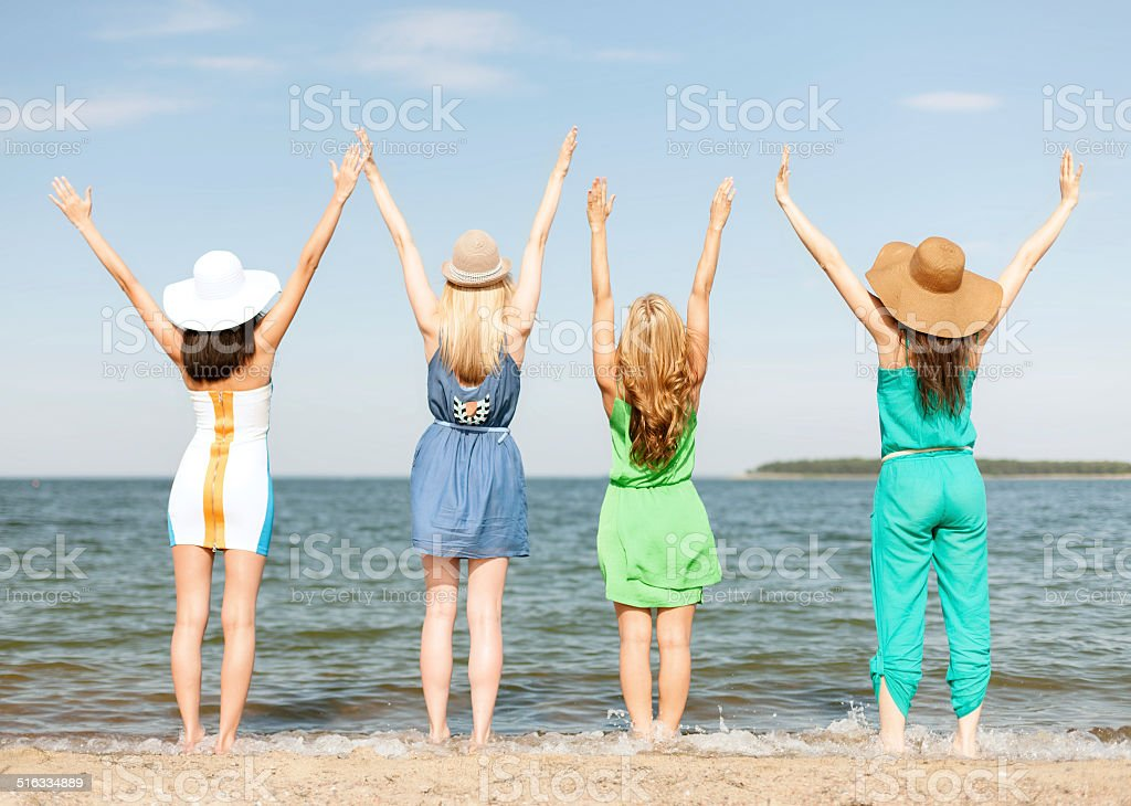 girls with hands up on the beach stock photo