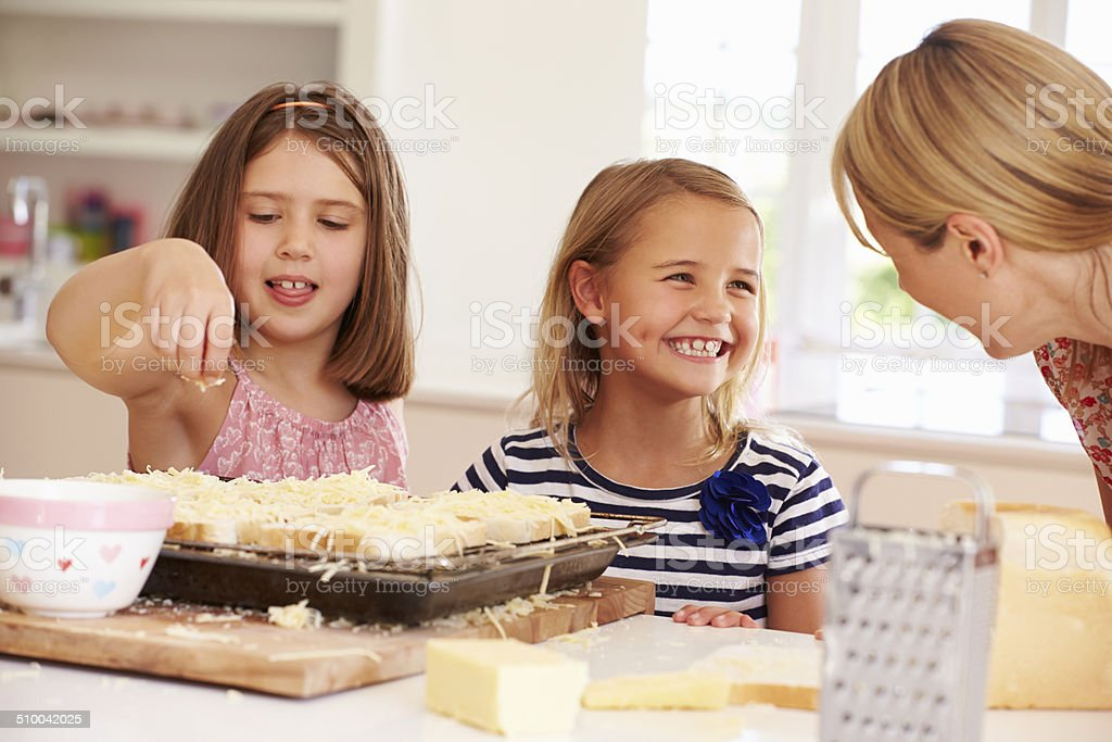 Girls With Mother Making Cheese On Toast stock photo