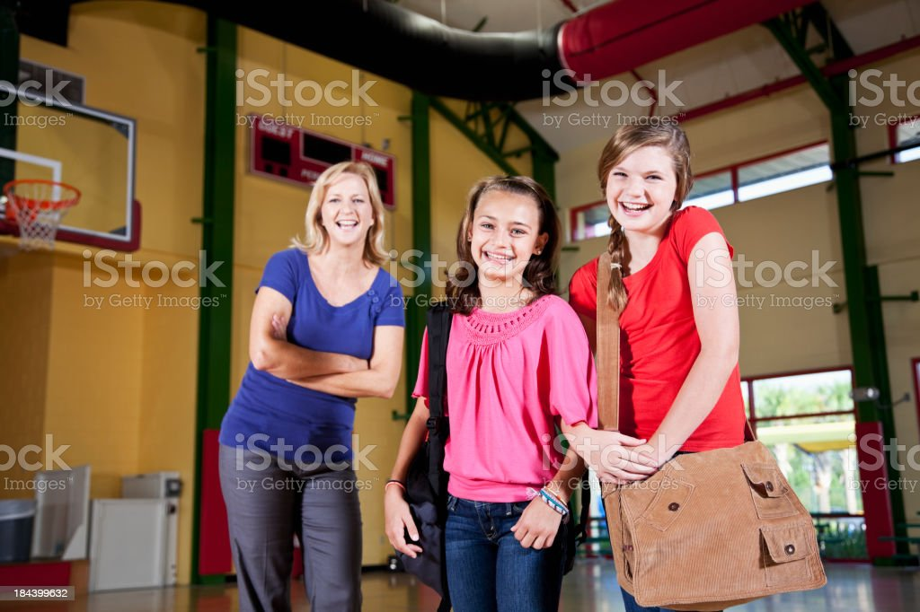 Girls with mother or teacher standing in school gym stock photo
