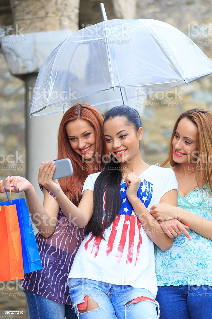 Girls with purchases making selfie under the rain stock photo