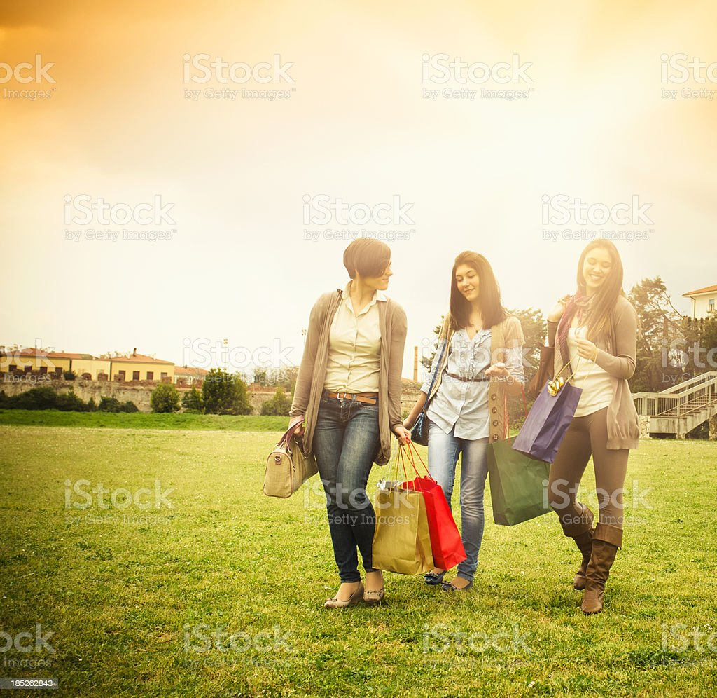 Girls with shopping bag walking on the grass royalty-free stock photo