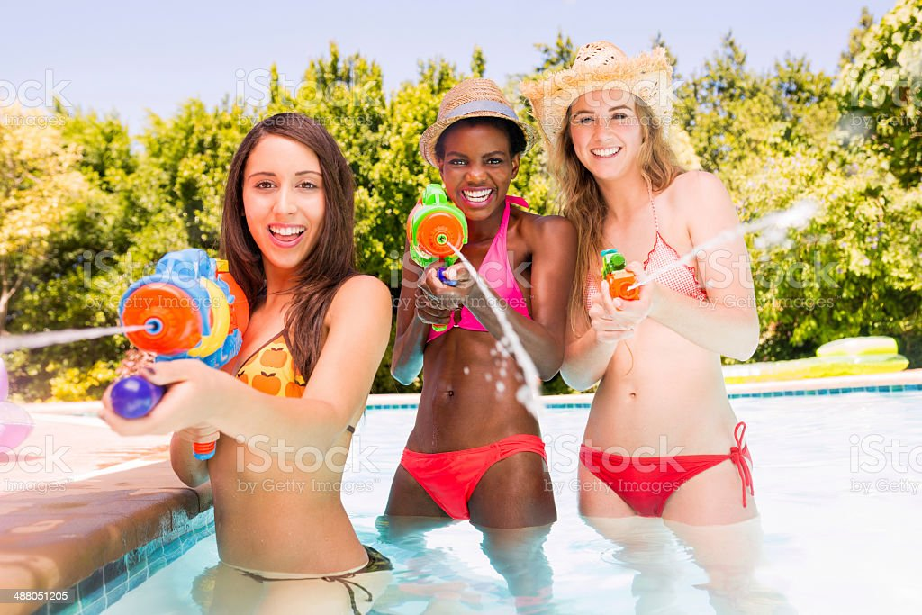 Girls with squirt gun in swimming pool stock photo