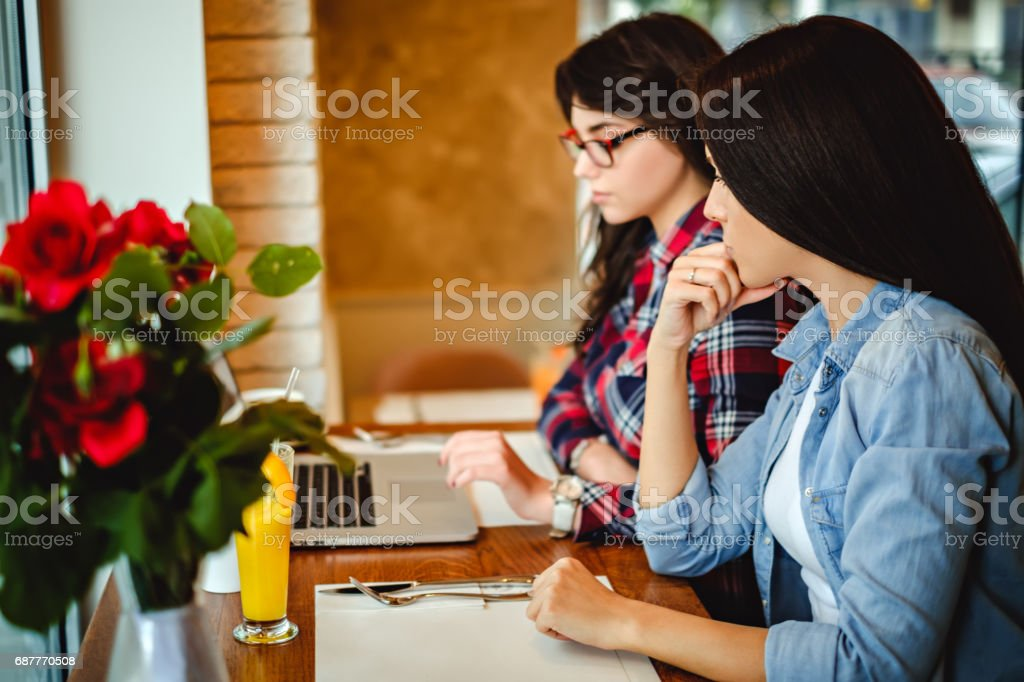 Girls working on a laptop in a cafe stock photo