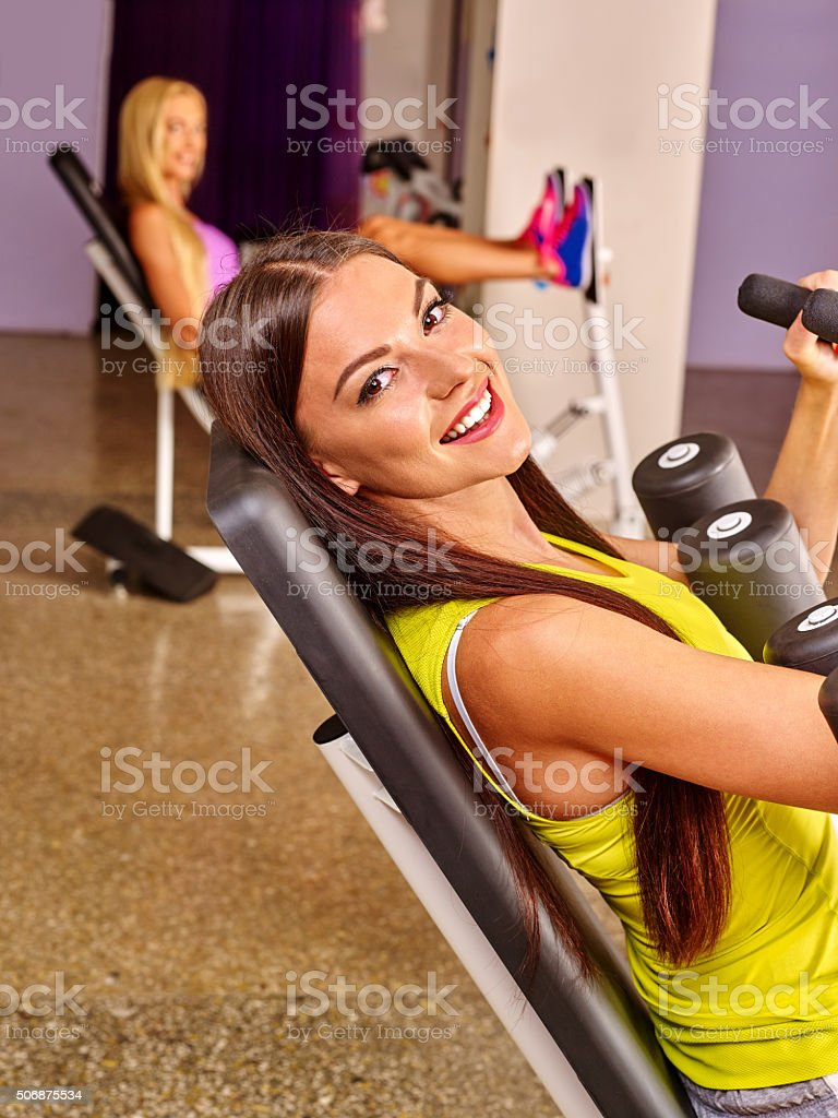 Girls workout on leg press in sport gym stock photo